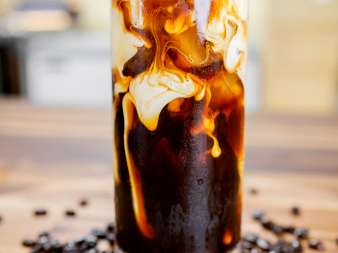 Merit Auto Spa Cafe Iced Coffee with Heavy Cream on Walnut Counter Table